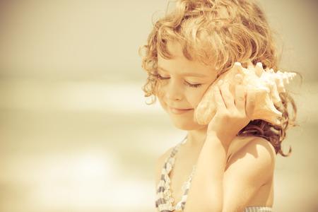 Foto de Happy child listen to seashell at the beach. Summer vacations concept - Imagen libre de derechos