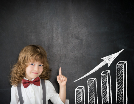 Foto de Smart kid in class. Happy child against blackboard. Drawing growth bar graph. Business concept - Imagen libre de derechos