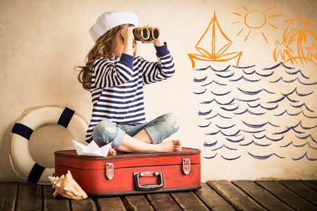Photo for Happy kid playing with toy sailing boat indoors. Travel and adventure concept - Royalty Free Image