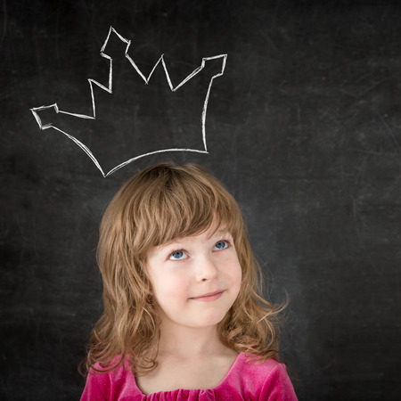 Photo pour Funny child against blackboard. Smiling girl with drawing crown - image libre de droit