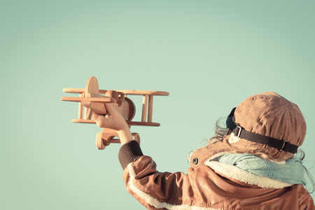Photo pour Happy child playing with toy wooden airplane against autumn sky background. Retro toned - image libre de droit
