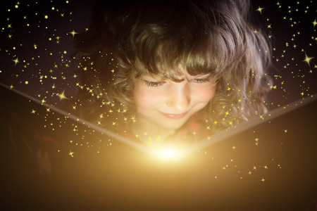 Photo for Happy kid reading magic book - Royalty Free Image
