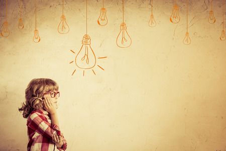 Photo pour Hipster kid thinking. Idea concept. Drawing bulb lump. Retro toned - image libre de droit