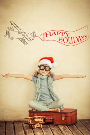 Foto de Happy child in Santa Claus hat playing with toy airplane at home. Retro toned - Imagen libre de derechos
