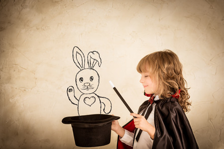 Photo pour Child magician holding a top hat with drawn rabbit against grunge background. Focus on the hat - image libre de droit