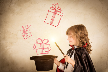 Photo pour Child magician holding a top hat with drawn gift boxes. Christmas holiday concept - image libre de droit