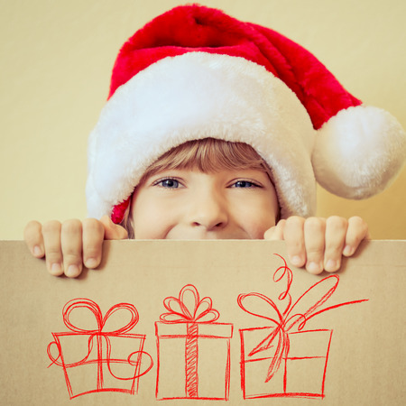Foto de Child holding Christmas card with drawn gift boxes. Xmas holiday concept - Imagen libre de derechos