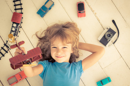 Foto de Child playing with vintage toys at home. Girl power and feminism concept - Imagen libre de derechos
