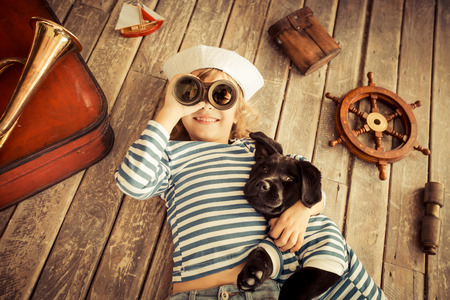 Photo pour Happy kid dressed in sailor. Child playing with dog at home. Travel and adventure concept - image libre de droit