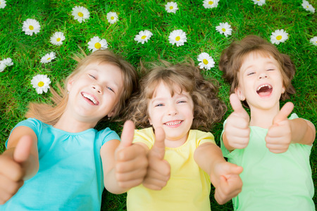 Photo for Happy children lying on green grass in spring park. Laughing kids showing thumbs up - Royalty Free Image