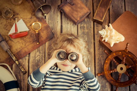 Photo pour Happy kid playing with nautical things. Child having fun at home. Travel and adventure concept. Unusual high angle view portrait - image libre de droit
