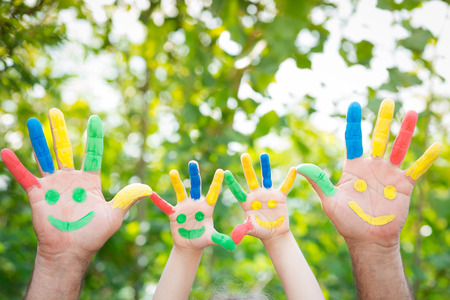 Photo for Smiley on hands against green spring background. Family having fun outdoors - Royalty Free Image