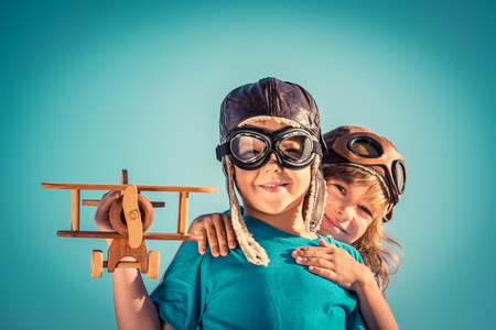 Foto per Happy kids playing with vintage wooden airplane outdoors. Portrait of children against summer sky background. Travel and freedom concept. Retro toned - Immagine Royalty Free