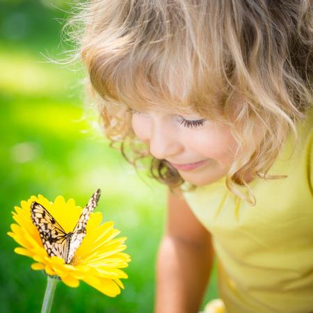 Foto de Beautiful child with butterfly in spring park. Happy kid playing outdoors - Imagen libre de derechos