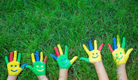 Foto de Group of happy people on green grass. Family having fun in spring. Smiley on hands. Ecology concept. Top view portrait - Imagen libre de derechos