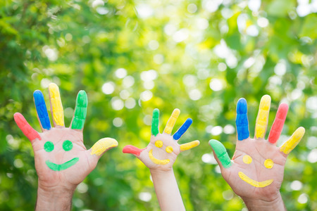Foto de Smiley on hands against green spring background. Family having fun outdoors - Imagen libre de derechos