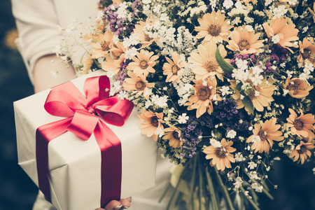 Foto de Gift box and flowers in hands against spring background. Family holiday concept. Mothers day - Imagen libre de derechos