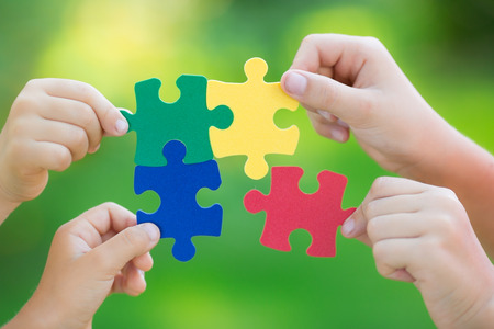 Photo pour Multicolor puzzles in hands against green spring blurred background. Teamwork and solution concept - image libre de droit