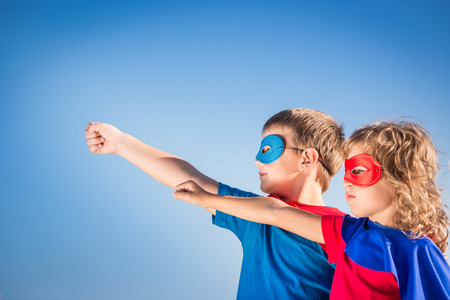 Photo pour Superhero children against summer sky background. Kids having fun outdoors. Boy and girl playing. Success and winner concept - image libre de droit