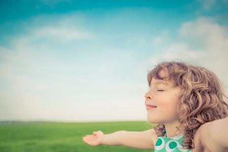Foto de Happy child in spring field. Young girl relax outdoors. Freedom concept - Imagen libre de derechos