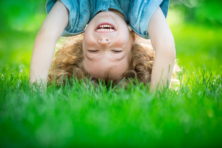 Foto de Happy child standing upside down on green grass. Laughing kid having fun in spring park. Healthy lifestyle concept - Imagen libre de derechos