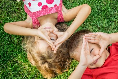 Foto de Happy children having fun outdoors. Kids playing in spring park. Boy and girl lying on green grass - Imagen libre de derechos