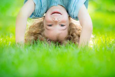 Photo for Happy child standing upside down on green grass. Laughing kid having fun in spring park. Healthy lifestyle concept - Royalty Free Image