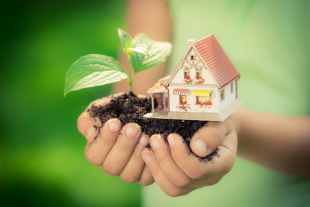Photo for Child holding house and tree in hands against spring green background. Real estate concept - Royalty Free Image