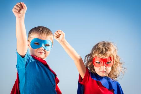 Foto de Superhero children against summer sky background. Kids having fun outdoors. Boy and girl playing. Success and winner concept - Imagen libre de derechos