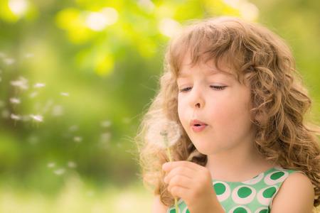 Foto de Beautiful child with dandelion flower in spring park. Happy kid having fun outdoors - Imagen libre de derechos