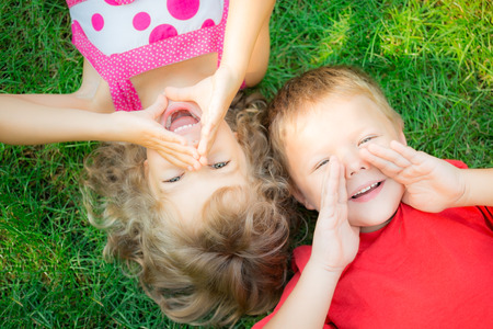 Photo pour Funny kids shouting outdoors. Happy children lying on green grass. Communication concept - image libre de droit