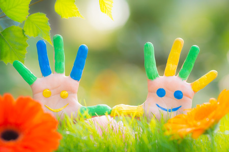 Foto de Happy smiley on hands against green spring background - Imagen libre de derechos