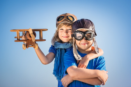 Photo pour Happy kids playing with vintage wooden airplane. Portrait of children against summer sky background - image libre de droit