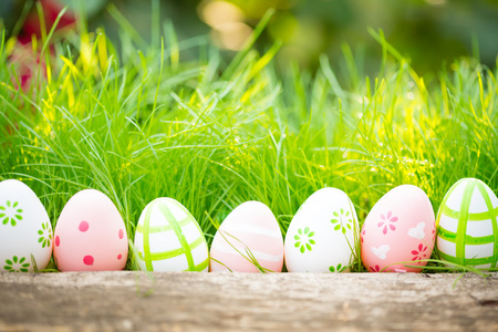Easter eggs in grass against blurred green background. Spring holidays concept