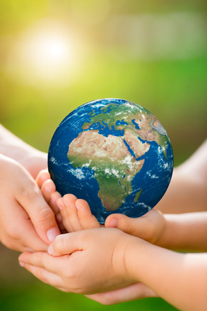 Photo pour Children holding 3D planet in hands against green spring background. Earth day holiday concept.  - image libre de droit