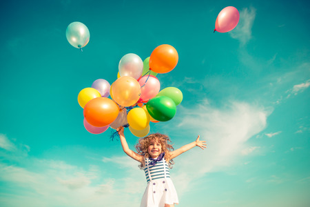 Photo for Happy child jumping with colorful toy balloons outdoors. Smiling kid having fun in green spring field against blue sky background. Freedom concept - Royalty Free Image