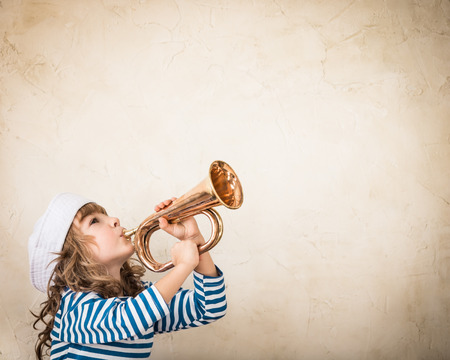 Photo pour Happy child blowing vintage nautical horn. Kid having fun at home. Summer sea dream and imagination. Adventure and travel concept. Retro toned image - image libre de droit