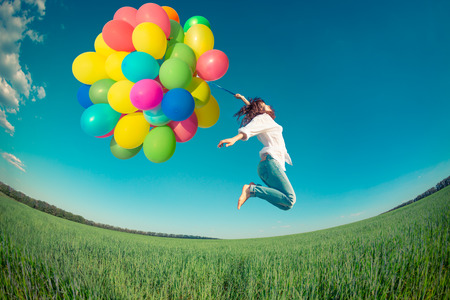 Foto de Happy girl jumping with colorful toy balloons outdoors. Young woman having fun in green spring field against blue sky background. Freedom concept - Imagen libre de derechos