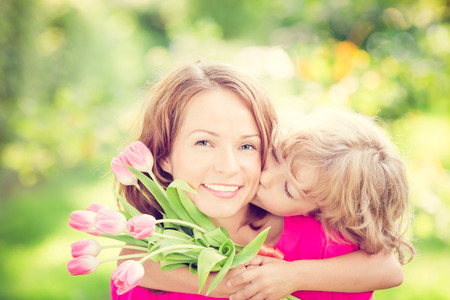 Foto de Woman and child with bouquet of flowers against green blurred background. Spring family holiday concept. Women's day - Imagen libre de derechos