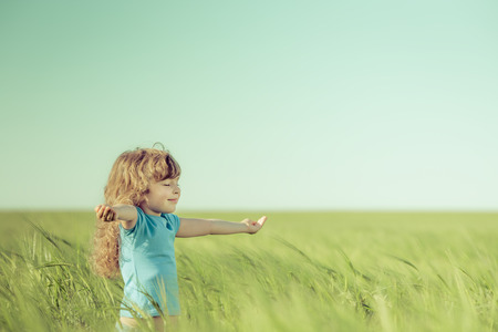 Foto de Happy child in spring field. Young girl relax outdoors. Freedom concept - Imagen libre de derechos
