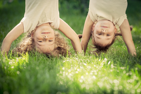 Foto de Happy children standing upside down on green grass. Smiling kids having fun in spring park. Healthy lifestyle concept - Imagen libre de derechos