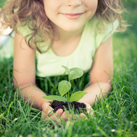 Photo pour Child holding young green plant in hands. Kid lying on grass in spring park. Earth day concept - image libre de droit