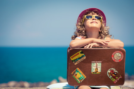 Photo pour Child with vintage suitcase on summer vacation. Travel and adventure concept - image libre de droit