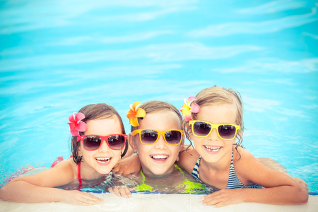 Foto de Happy children in the swimming pool. Funny kids playing outdoors. Summer vacation concept - Imagen libre de derechos