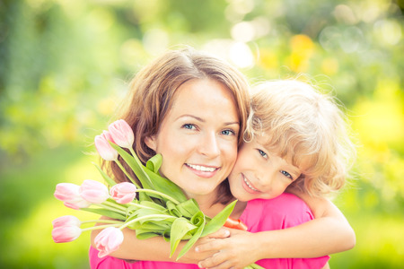 Photo for Mother and daughter with bouquet of flowers against green blurred background. Spring family holiday concept. Mother's day - Royalty Free Image