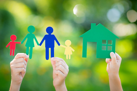 Foto de Paper house and family in hand against spring green background. Real estate business concept - Imagen libre de derechos