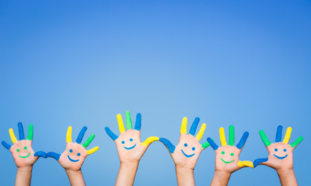 Photo pour Happy people with smiley on hands against blue summer sky background - image libre de droit