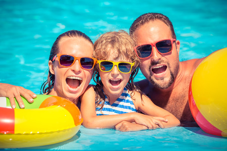 Happy family playing in swimming pool. Summer vacation concept
