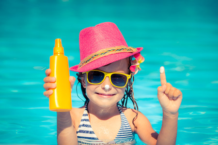Photo for Happy child holding sunscreen lotion in hand. Summer vacations concept - Royalty Free Image