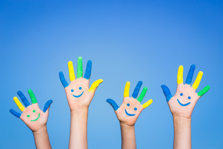 Photo pour Happy family with smiley on hands against blue summer sky background - image libre de droit